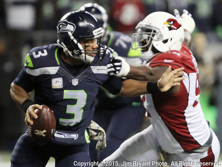 Seattle Seahawks  quarterback Russell Wilson (3) scrambles away from Arizona Cardinals defensive Calais Campbell (93) at CenturyLink Field in Seattle, Washington on November 15, 2015. The Cardinals beat the Seahawks 39-32.   ©2015. Jim Bryant photo. All Rights Reserved.