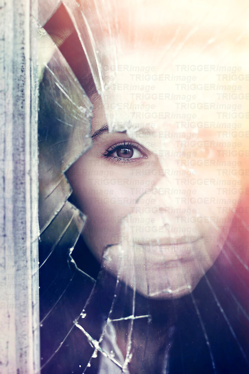 A woman looks through a colourful broken window.