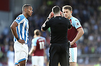 Referee Christopher Kavanagh has words with Huddersfield Town's Mathias Zanka Jorgensen (left) and Burnley's James Tarkowski<br /> <br /> Photographer Rich Linley/CameraSport<br /> <br /> The Premier League - Burnley v Huddersfield Town - Saturday 6th October 2018 - Turf Moor - Burnley<br /> <br /> World Copyright &copy; 2018 CameraSport. All rights reserved. 43 Linden Ave. Countesthorpe. Leicester. England. LE8 5PG - Tel: +44 (0) 116 277 4147 - admin@camerasport.com - www.camerasport.com
