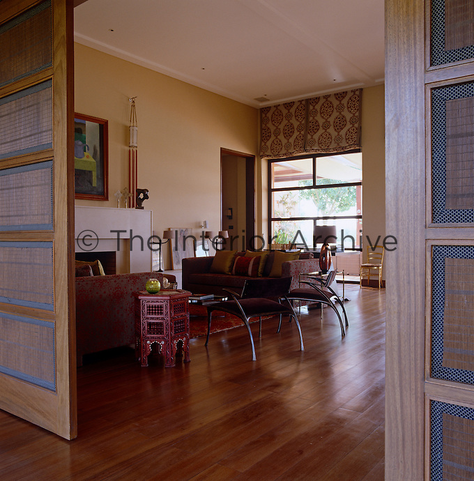 Panelled screens open from a long corridor revealing a spacious living area