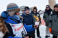 After successfully completing this year's Iditarod, Cindy Gallea ceremoniously burns last year's scratch paperwork at the finish line in Nome on Sunday  March 22, 2015 during Iditarod 2015.  <br /> <br /> (C) Jeff Schultz/SchultzPhoto.com - ALL RIGHTS RESERVED<br />  DUPLICATION  PROHIBITED  WITHOUT  PERMISSION