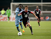 Kei Kamara (23) of Sporting KC fights for the ball with Daniel Woolard (21) of D.C. United during the game at RFK Stadium in Washington, DC.  Sporting KC defeated D.C. United, 1-0.