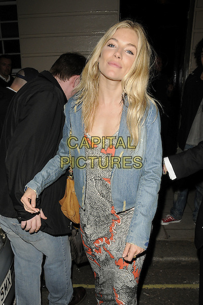 "SIENNA MILLER .seen leaving after the evening performance of ""Flare Path"", Theatre Royal Haymarket, London, England, UK, May 20th 2011..half length  denim jacket white black orange print dress   .CAP/CAN.©Can Nguyen/Capital Pictures."