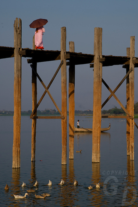 A buddhist Nun crossing the U-Bein Bridge, the teakwood bridge spans 1.2 km across the shallow Taungthaman Lake some 10 km south of Mandalay. Amanpura, Mandalay, Myanmar/Burma