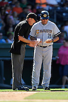 Manager Luis Dorante (25) of the Charleston RiverDogs talks with umpire Todd Drake between innings in a game against the Greenville Drive on Sunday, June 28, 2015, at Fluor Field at the West End in Greenville, South Carolina. Charleston won, 12-9. (Tom Priddy/Four Seam Images)