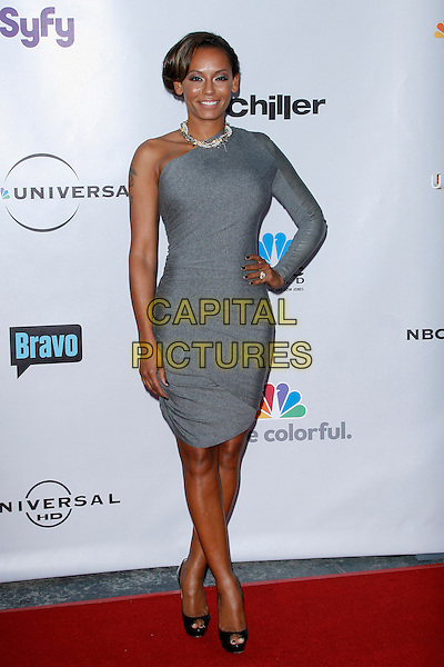 MELANIE BROWN (MEL B). arriving at the The Cable Show 2010 To Feature An Evening With NBC Universal held at  Universal Studios Hollywood in Universal City, California, USA, .May 12th, 2010..full length grey gray one shoulder sleeve dress black peep toe platform shoes christian louboutin hand on hip .CAP/ROT/AMB.©Adriana M. Barraza /Roth Stock/Capital Pictures