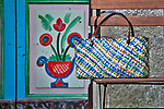 A multi colored straw bag from Bellagio, Italy on a chair by a painted door