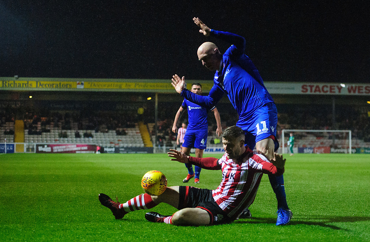 Lincoln City's Michael O'Connor is fouled by Morecambe's Alex Kenyon<br /> <br /> Photographer Chris Vaughan/CameraSport<br /> <br /> The EFL Sky Bet League Two - Saturday 15th December 2018 - Lincoln City v Morecambe - Sincil Bank - Lincoln<br /> <br /> World Copyright © 2018 CameraSport. All rights reserved. 43 Linden Ave. Countesthorpe. Leicester. England. LE8 5PG - Tel: +44 (0) 116 277 4147 - admin@camerasport.com - www.camerasport.com