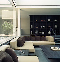 In the open-plan living room light floods in through one of the plate glass windows surrounding the inner courtyard