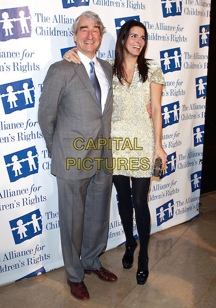SAM WATERSTON & ANGIE HARMON.The Alliance For Children's Right Dinner Gala held at  The Beverly Hilton Hotel, Beverly Hills, CA, USA..February 10th, 2010.full length suit jacket grey gray white cream dress black tights hand on hip beads beaded silver arm over shoulder blue tie .CAP/ADM/TC  .©T.Conrad/AdMedia/Capital Pictures.