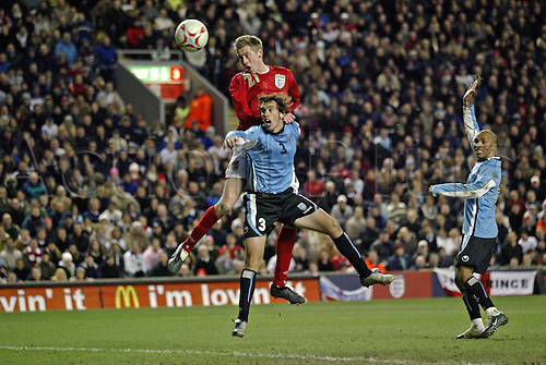 1 March 2006: England striker Peter Crouch jumps above Diego Godin to score England's equalising goal during the International friendly match between England and Uruguay played at Anfield, Liverpool. England won the game 2-1 Photo: Glyn Kirk/Actionplus...060301 football soccer player headers scoring.
