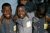 Lusaka, Zambia; three smiling boys wearing uniform shirts of the Jacaranda school.