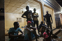AGADEZ, NIGER &mdash; <br /> A group of migrants from Cameroon prepares to settle for the night a the bus station in Agadez, Niger. They were retuning from Arlit, a city north of Agadez which is situated in the middle of the Sahara desert. This group was traveling north with a smuggler in their attempt to reach Italy through Libya. As they approached Arliz, they ran into a police check point. They were promptly turned back after the police stole all their money and threatened to keep their travel documents if they didn't turn back. Without a dime to their name, they were forced to sleep on the Agadez bus station along dozens of other migrants before figuring out their next move.