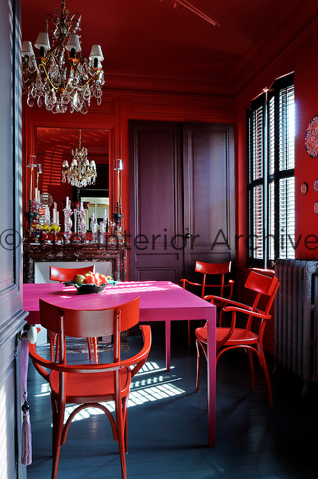 The dining room is an explosion of colour with red lacquer chairs surrounding a fuschia pink table