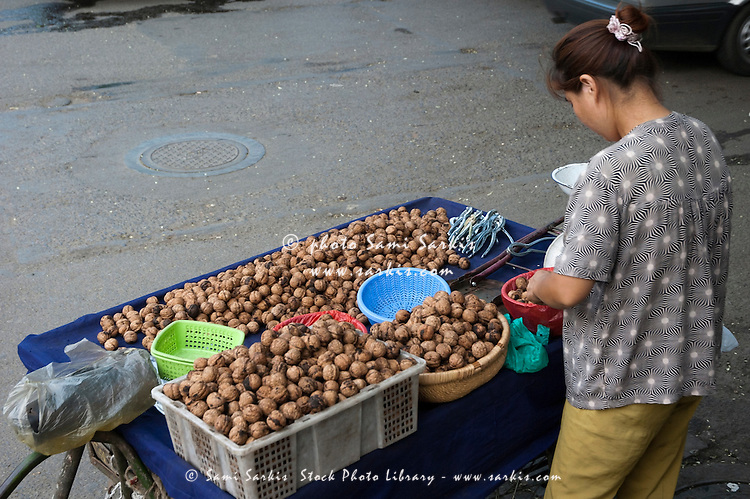 Woman selling walnuts in the street in the Muslim district of Daqingzhen Si in Xi'an, Shaanxi, China.