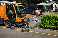 Switzerland. Canton Ticino. Tenero. Camping Campofelice. Garbage collectors. Streets cleaning. A street sweeper drives a street brooming machine on the road. The worker and his machine pass by a woman holding a broom in her right hand and a plastic Merfen (Antiseptics) ball with a swiss flag in between her legs. A campervan (or camper van), sometimes referred to as a camper, or a caravanette, is a self-propelled vehicle that provides both transport and sleeping accommodation. A motorhome (or motor coach is a type of self-propelled recreational vehicle (RV) which offers living accommodation combined with a vehicle engine. Motorhomes are part of the much larger associated group of mobile homes which includes caravans, also known as tourers, and static caravans. A caravan, travel trailer, camper or camper trailer is towed behind a road vehicle to provide a place to sleep which is more comfortable and protected than a tent. It provides the means for people to have their own home on a journey or a vacation. Campers are restricted to designated sites for which fees are payable. The flag of Switzerland consists of a red flag with a white cross (a bold, equilateral cross) in the centre. It is one of only two square sovereign-state flags. 20.07.2018 © 2018 Didier Ruef