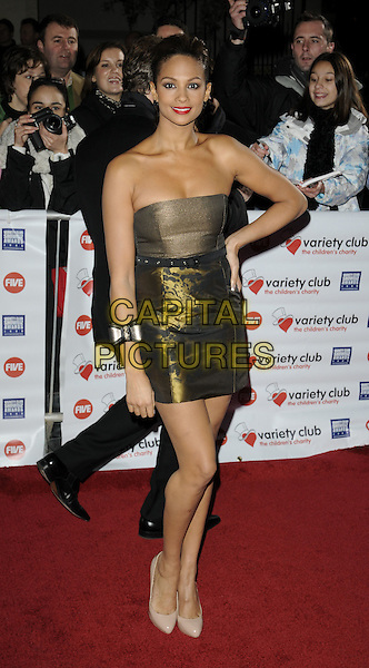 ALESHA DIXON.At the Variety Club Showbiz Awards held at the Grosvenor House Hotel, Park Lane, London, England..November 15th 2009.full length strapless gold dress hand on hip beige shoes patent christian louboutin heels bow cuff bracelet black print pattern .CAP/CAN.©Can Nguyen/Capital Pictures.