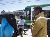 Ethiopia. Addis Ababa. A muslim couple and other passengers wait on tramway station. Addis Ababa Light Rail is a light rail transportation system in Addis Ababa. A 17-kilometre line running from the city centre to industrial areas in the south of the city opened on 20 September 2015. Service began on 9 November 2015 for the second line (west-east). The total length of both lines is 32 kilometres with 32 stations. Trains are expected to be able to reach maximum speeds of 70 km/h. The railway was contracted by the China Railway Group Limited and is nowdays operated by the Shenzhen Metro Group. The Ethiopian Railways Corporation began construction of the double track electrified light rail transit project in December 2011 after securing funds from the Export-Import Bank of China. This light-rail system was the first to be built in sub-saharan Africa. Addis Ababa is the capital city and the name of a region of Ethiopia. The moslem woman wears the niqab and the abaya. The abaya, sometimes also called aba, is a simple, loose over-garment, essentially a robe-like dress, worn by some women in parts of the Islamic world. The abaya covers the whole body except the face, feet, and hands. It can be worn with the niqab, a face veil covering all but the eyes. A niqab is a cloth which covers the face, worn by some Muslim women as a part of sartorial hijab. 20.11.15 © 2015 Didier Ruef