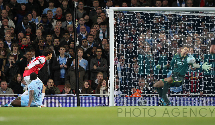 Arsenals Ju Young Park sees his shot saved by Manchester Citys Costel Pantilimon .