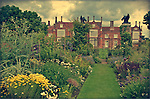 Summers day in Helmingham Hall gardens with flower boarders and moat