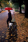 Woman running across street holding an umbrella jumping over puddles and leaves Seattle Washington State USA