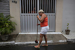 RECIFE, BRAZIL - JANUARY 9: Rosangela Gonsalves, 53, sweeps rain water from the gutter to drain, outside her neighbor's home, in Recife, Pernambuco, Brazil, on Saturday, Jan. 9, 2016.<br /> <br /> The mosquito-borne Zika virus continues to spread in Brazil, alarming health officials and expecting mothers that their babies will be born with abnormal brain development called microcephaly. While researchers have yet to make a connection, Brazil has the highest number of babies born with mircocephaly - the most cases in Recife, Pernambuco - from mothers who tested positive to the Zika virus.