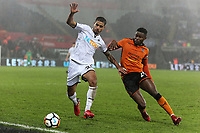 (L-R) Kyle Naughton of Swansea City challenged by Bright Enobakhare of Wolverhampton Wanderers during the Emirates FA Cup match between Swansea and Wolverhampton Wanderers at the Liberty Stadium, Swansea, Wales, UK. Wednesday 17 January 2018