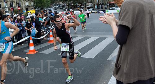 10 JUL 2011 - PARIS, FRA - Mathieu Bigaud salutes the crowd as he crosses the Pont de l'Alma during the Triathlon de Paris .(PHOTO (C) NIGEL FARROW)