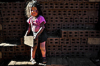 A 5-year-old Peruvian girl carries bricks at a brick factory in the outskirts of Puno, Peru, 6 August 2012. Child labour is a common practice at the artisanal brick factories, found predominantly in socially deprived areas of the urban zones. Poverty and lack of employment force parents, mainly season workers coming from rural areas of the country, to employ their own children, in an effort to ensure the livelihood for the whole family. Children aged 4-7 take part in simple jobs while children aged 8 and up tend to work regularly, same as adults. A family group, consisting of 2 adults and 2-3 children, may earn 20-25 USD per day, working almost the whole day, often in harsh climatic conditions.