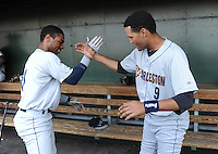 Infielder Angelo Gumbs (21) of the Charleston RiverDogs, left, slaps hands with teammate outfielder Mason Williams (9) in the dugout just before a game against the Greenville Drive on May 31, 2012, at Fluor Field at the West End in Greenville, South Carolina. Charleston won, 13-2.  (Tom Priddy/Four Seam Images)