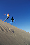 Two young men jumping off sand dune ridge; Oregon Dunes National Recreation Area, Umpqua Dunes section, Oregon coast.