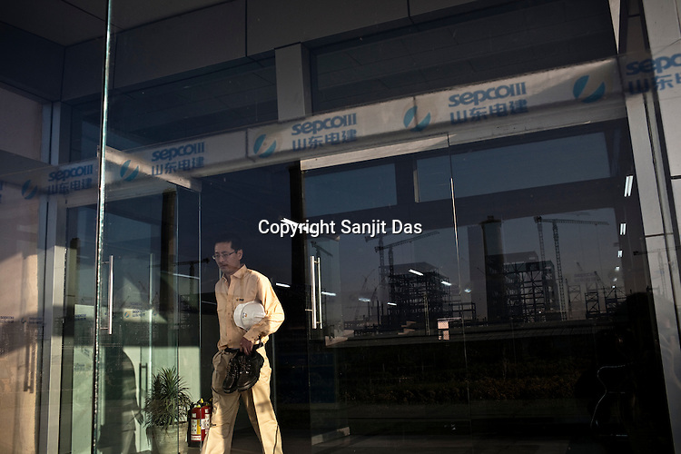 A Chinese engineer from Sepco walks out of the Chinese office at the construction site of the Adani Power plant of 4620 MW capacity in Mundra port industrial city of Gujarat, India. Indian power companies have handed out dozens of major contracts to Chinese firms since 2008. Adani Power Ltd have built elaborate Chinatowns to accommodate Chinese workers, complete with Chinese chefs, ping pong tables and Chinese television. Chinese companies now supply equipment for about 25% of the 80,000 megawatts in new capacity.