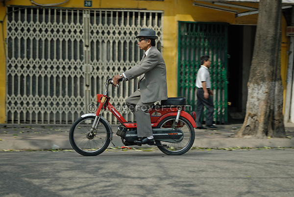 Asia, Vietnam, Hanoi. Hanoi old quarter. Old vietnamese man wearing a suit and hat on small Peugeot motorbike (moped).