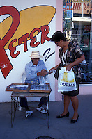 Woman buying a lottery ticket from a street vendor in Penonome, Panama