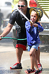 Madelyn Slaney, 6, takes aim with the hose as she participates in the water fights with the assistance of Carey Severson of the Black Earth Fire Department.