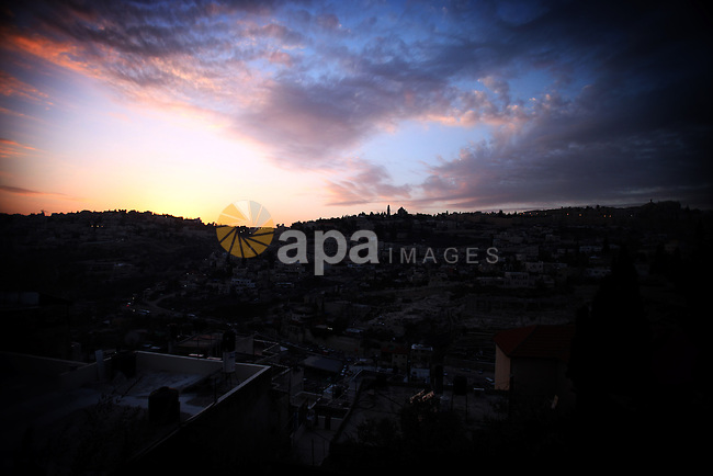 A sunset is seen over Silwan neighborhood, in Jerusalem on December 26, 2013. Photo by Saeed Qaq