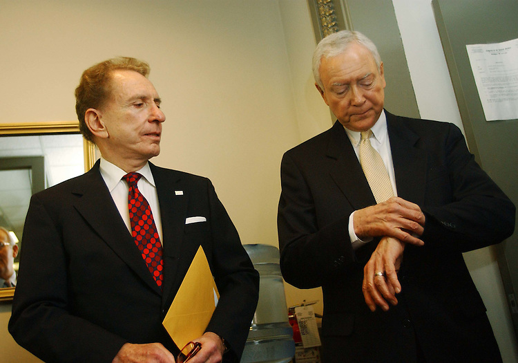 "11/18/04.SPECTER SUPPORT--Sen. Arlen Specter, R-Pa., and outgoing Chairman Orrin G. Hatch, R-Utah, checking watch, wait for other senators for a news conference in which Senate Judiciary Republicans announced their unanimous support for Specter as their next chairman..From CQ.com: ""We are definitely supporting Arlen Specter for this position,"" said Orrin G. Hatch, R-Utah, who is being forced by six-year GOP term limits to relinquish the chairmanship. ""He will be the chairman of the Senate Judiciary Committee."".Social conservatives have bombarded Senate Republicans with demands that they block Specter from becoming chairman ever since he said Nov. 3 that President Bush would have a difficult time winning confirmation of any Supreme Court nominee who was eager to overturn the landmark 1973 Roe v. Wade decision legalizing abortion nationwide..Though the actual chairmanship vote will not take place until the new Congress convenes in January, Thursday's announcement appears to assure that Specter will survive the conservative onslaught. Committee Republicans have the first vote on the chairmanship, and their recommendation must then be approved by a majority of the 55 Republicans who will serve in the 109th Congress..Flanked by his fellow committee Republicans, Specter read a statement in which he said, ""I have not and would not use a litmus test to confirm nominees."".CONGRESSIONAL QUARTERLY PHOTO BY SCOTT J. FERRELL"