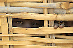 Displaced boys peer through a fence around a feeding center for malnourished children in the Bilel camp near Nyala..