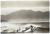 MEXICO,  Baja, silhouette of man surfing on wave at El Cerritos (B&W)