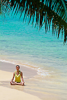 Woman on white sand beach in meditation pose under green palm tree