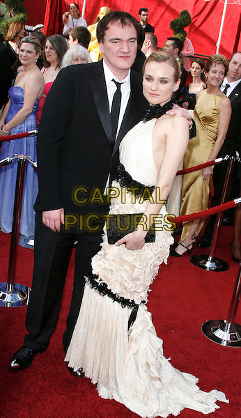 QUENTIN TARANTINO & DIANE KRUGER.The 82nd Annual Academy Awards held aat The Kodak Theatre in Hollywood, California, USA..March 7th, 2010.oscars full length black dress white drop waist fishtail frills lace halterneck sleeveless suit side clutch bag .CAP/EAST.©Eastman/Capital Pictures.