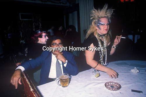 Titanic Club London. 1980s 1983. New Romantic punk woman with Asian businessman.