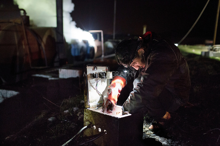 17/02/15 --TANJERO, IRAQ: Sorbets (22) adjusts the electric fuel pump at night.<br /> <br /> The family of Yezidis, displaced from Sinjar, live next to an oil refinery in the Kurdish Region of Iraq. The young men run the refinery 24 hours a day with little to no safety equipment. Reporting for this article was supported by a grant from the Pulitzer Center on Crisis Reporting