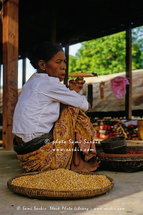 Mature woman smoking a cheroot cigar at a market, Bagan, Burma.