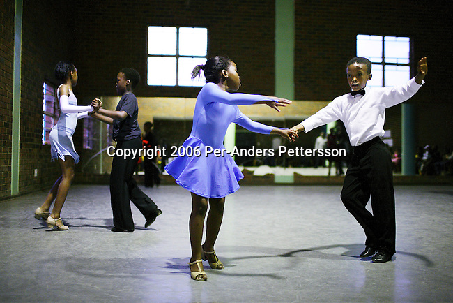 SOWETO, SOUTH AFRICA OCTOBER 25: Ballroom dancers rehearse in a community hall in Pimville Community center on October 25, 2006 in Soweto, Johannesburg, South Africa. Ballroom dancing is very popular sport in the township and all over the country. Soweto is South Africa?s largest township and it was founded about one hundred years to make housing available for black people south west of downtown Johannesburg. The estimated population is between 2-3 million. Many key events during the Apartheid struggle unfolded here, and the most known is the student uprisings in June 1976, where thousands of students took to the streets to protest after being forced to study the Afrikaans language at school. Soweto today is a mix of old housing and newly constructed townhouses. A new hungry black middle-class is growing steadily. Many residents work in Johannesburg, but the last years many shopping malls have been built, and people are starting to spend their money in Soweto.  .(Photo by Per-Anders Pettersson/Getty Images).