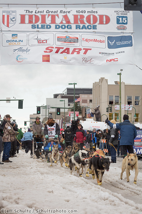 Trent Herbst and team leave the ceremonial start line with an Iditarider at 4th Avenue and D street in downtown Anchorage, Alaska during the 2015 Iditarod race. Photo by Jim Kohl/IditarodPhotos.com