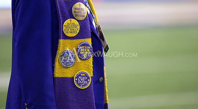 A Husky Marching Band staff member shows off buttons from past Washington-Oregon contests.