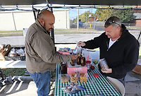 NWA Democrat-Gazette/DAVID GOTTSCHALK Alfredo Chapa (left) tries a new crop pecan Thursday, October 31, 2019, rom Jim Taylor before making a purchase at Taylor's Market on Janet Street in Springdale. The market carries seasonal items including the pecans, a variety of peanuts and other produce.