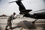 "A soldier washes down a Blackhawk during routine maintenance. Scenes from the medical evacuations of wounded Americans, Canadians, and Afghan civilians and soldiers being flown by Charlie Co. 6th Battalion 101st Aviation Regiment of the 101st Airborne Division. Charlie Co. - which flies under the call-sign ""Shadow Dustoff"" - flies into rush the wounded to medical care out of bases scattered across Oruzgan, Kandahar, and Helmand Provinces in the Afghan south. These images were taken of missions flown out of Kandahar Airfield in Kandahar Province and Camp Dwyer in Helmand Province."