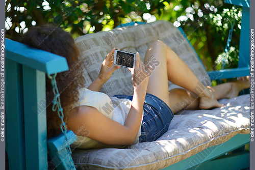 Young woman lying on a patio bench with an iPhone in her hands, watching a movie on the phone screen